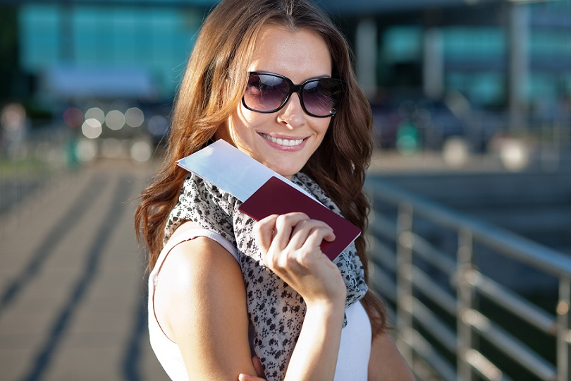 Cheerful tourist woman holding passport and ticket